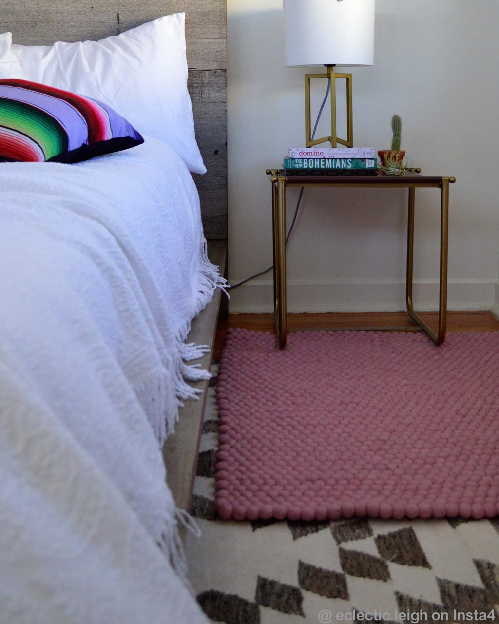 book on bed side table with lamp danish design pink felt ball capel rugs